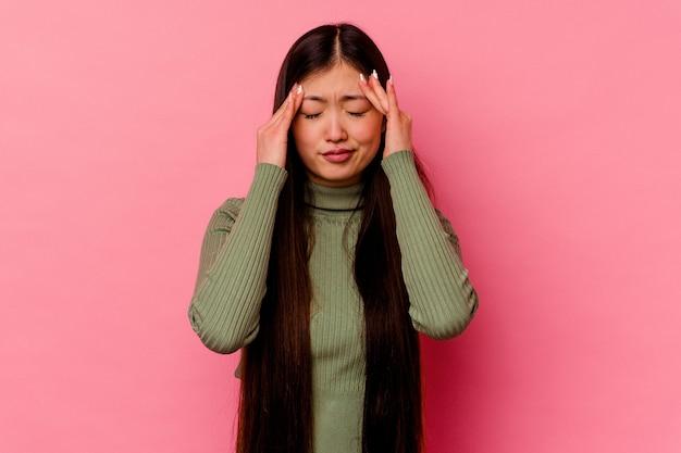 Молодая китаянка изолирована на розовом фоне, трогательно висков и имея головную боль.