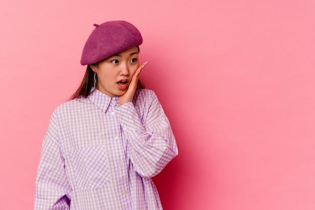 Молодая китаянка, изолированная на розовом, шокирована чем-то, что она видела.