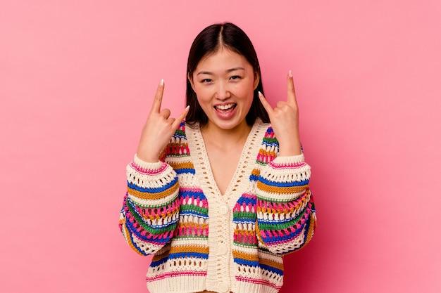혁명 개념으로 뿔 제스처를 보여주는 분홍색에 고립 된 젊은 중국 여자.