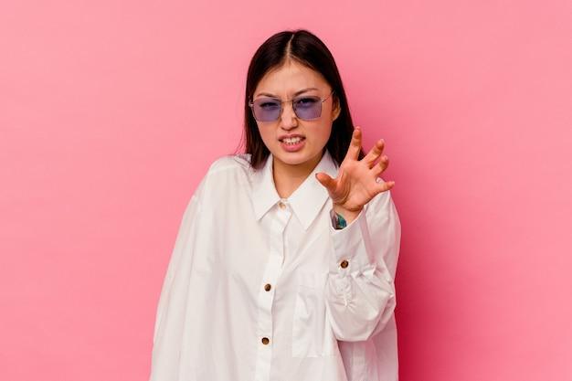 ピンクで隔離された若い中国人女性は、猫を模倣した爪、攻撃的なジェスチャーを示しています。