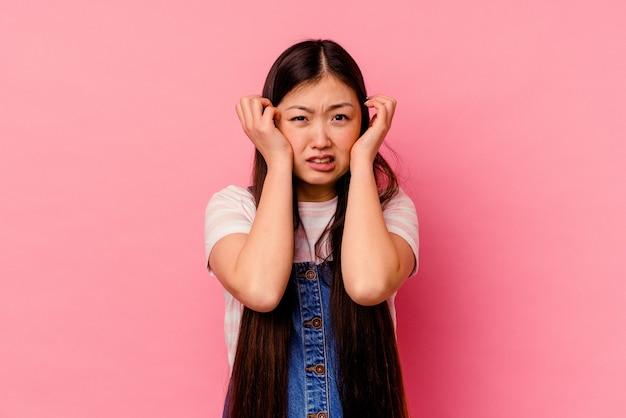 ピンクの壁に孤立した若い中国人女性が泣いて、何かに不満、苦痛と混乱の概念。