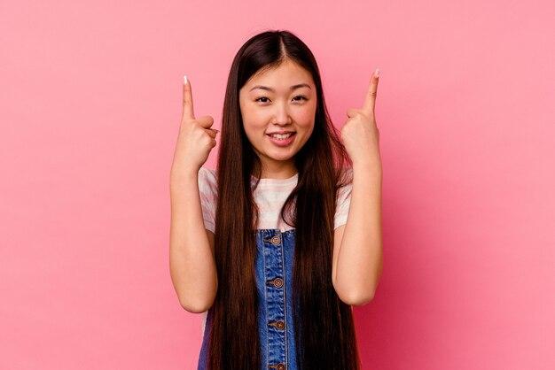 분홍색 벽에 고립 된 젊은 중국 여자는 빈 공간을 보여주는 두 앞 손가락으로 나타냅니다.