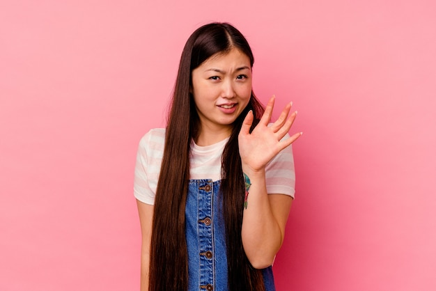 Молодая китаянка изолирована на розовой стене, отвергая кого-то, показывая жест отвращения.