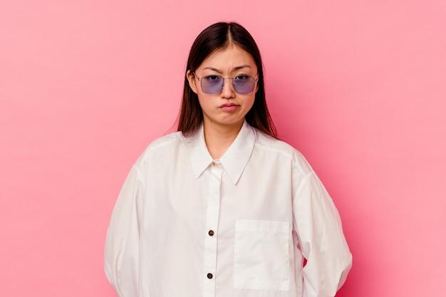 ピンクの壁に孤立した若い中国人女性悲しい、深刻な顔、悲惨で不快な感じ