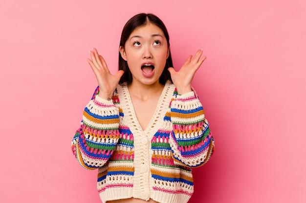 ピンクの壁に孤立した若い中国人女性が空に向かって叫び、見上げて、欲求不満