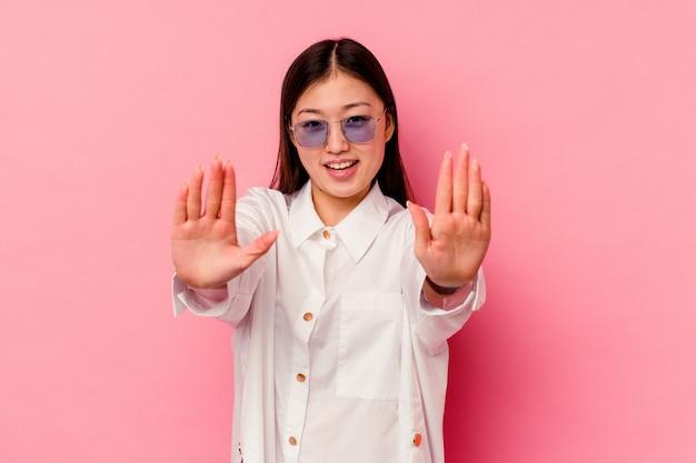 ピンクの壁に孤立した若い中国人女性が手で10番を示しています。