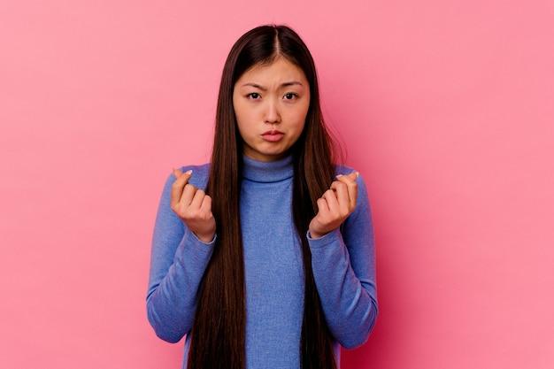 彼女はお金がないことを示すピンクの壁に孤立した若い中国人女性