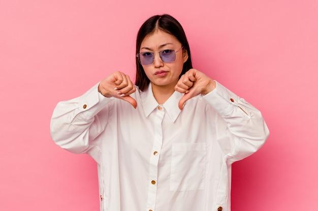 親指を下に示すピンクの壁に分離された若い中国人女性