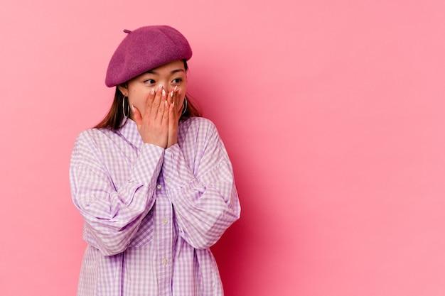 사려 깊은 분홍색 벽에 고립 된 젊은 중국 여자 손으로 입을 덮고 복사 공간을 찾고