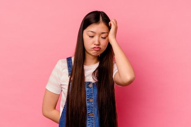 ピンクの壁に孤立した若い中国人女性は疲れていて、頭に手を置いて非常に眠い