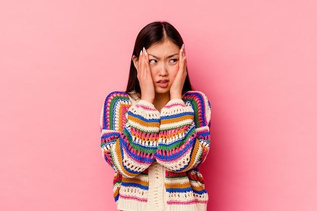 ピンクの壁に孤立した若い中国人女性が泣き叫び、悲しげに泣く