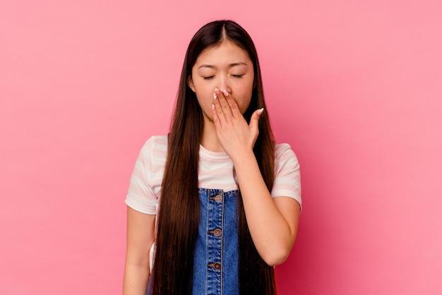 手で口を覆う疲れたジェスチャーを示すあくびをするピンクの壁に孤立した若い中国人女性