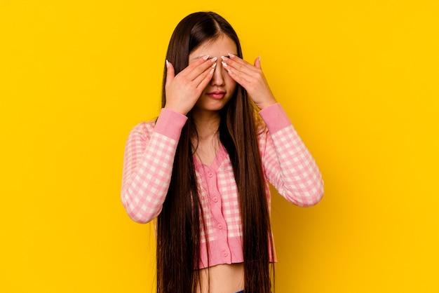 Молодая китаянка на желтом фоне боится закрывать глаза руками.