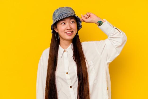 승리, 열정과 열정, 행복 한 식을 축 하하는 노란색 배경에 고립 된 젊은 중국 여자.