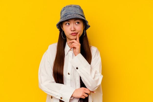고민, 전략 계획, 비즈니스 방법에 대해 생각하는 노란색 배경에 고립 된 젊은 중국 여자.
