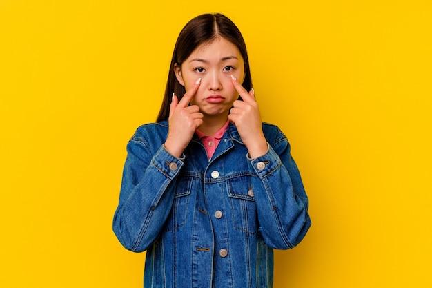 울고, 뭔가, 고통과 혼란 개념에 불만 노란색 배경에 고립 된 젊은 중국 여자.