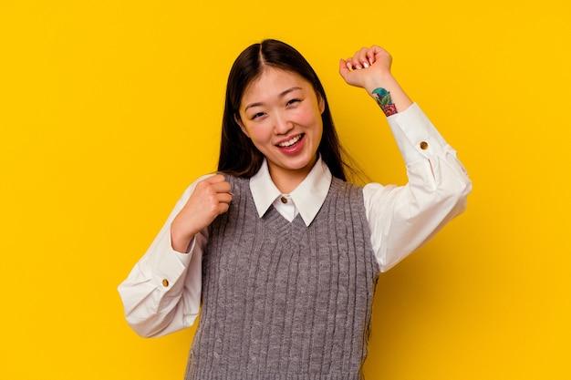 Молодая китаянка изолирована на желтом фоне, танцует и веселится.