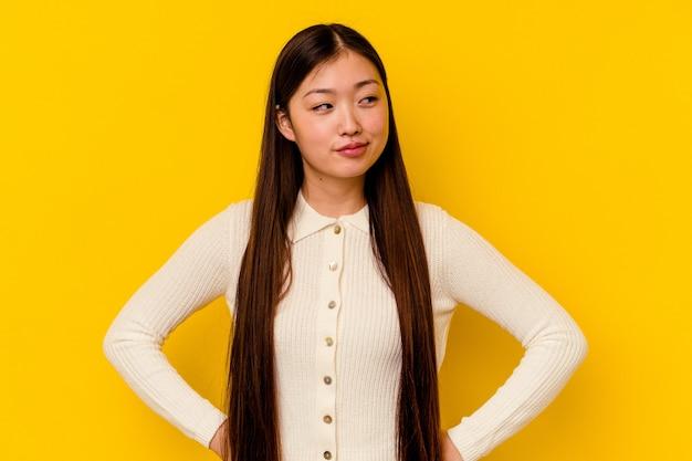 목표와 목적 달성을 꿈꾸는 노란색 배경에 고립 된 젊은 중국 여자