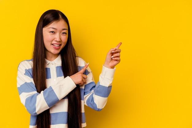 Молодая китаянка изолирована на желтом фоне взволнованно указывая указательными пальцами.