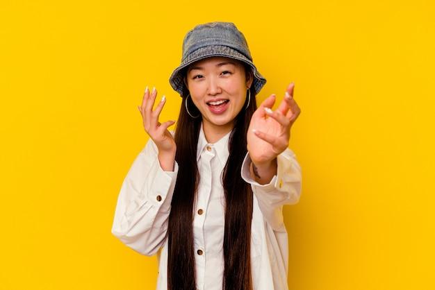黄色の背景で隔離の若い中国人女性は、カメラに抱擁を与える自信を持っています。