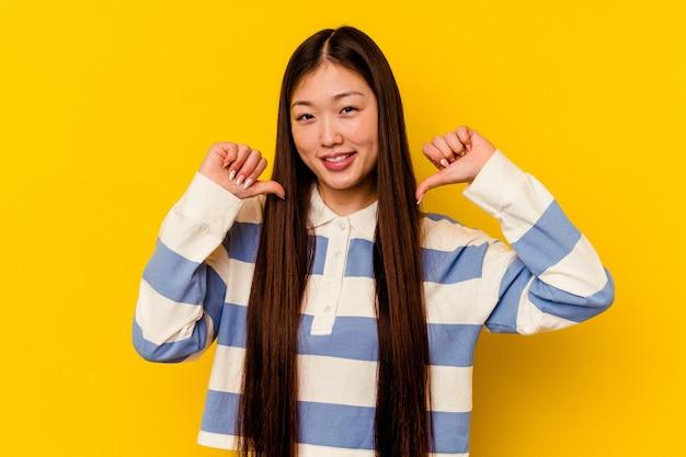 Молодая китаянка, изолированная на желтом фоне, чувствует гордость и уверенность в себе, пример для подражания.
