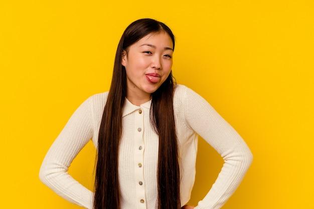 Молодая китаянка изолирована на желтом фоне, смешно и дружелюбно высунув язык.