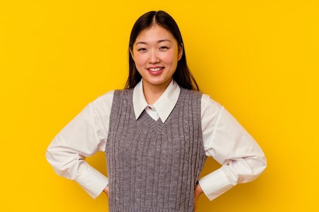 행복 하 고 웃 고 쾌활 한 노란색 배경에 고립 된 젊은 중국 여자.