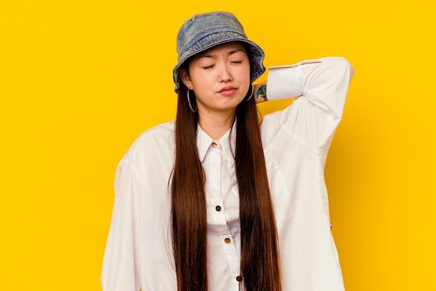 Молодая китаянка изолирована на желтом фоне с болью в шее из-за стресса, массируя и касаясь ее рукой.
