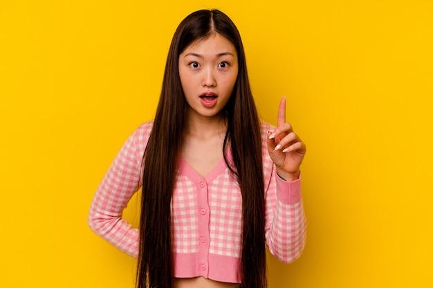 アイデア、インスピレーションの概念を持つ黄色の背景に分離された若い中国人女性。