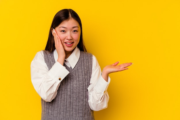 노란색 배경에 고립 된 젊은 중국 여자 손바닥에 복사 공간을 보유 하 고 뺨에 손을 유지합니다. 놀랍고 기뻐했습니다.