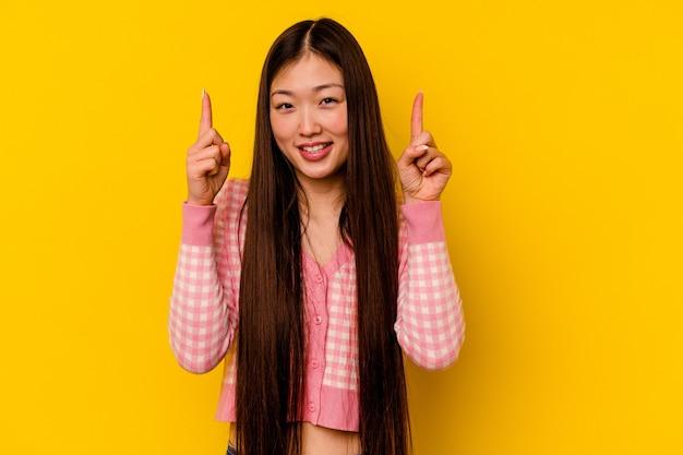 Молодая китаянка, изолированная на желтом фоне, показывает обоими указательными пальцами вверх, показывая пустое пространство.