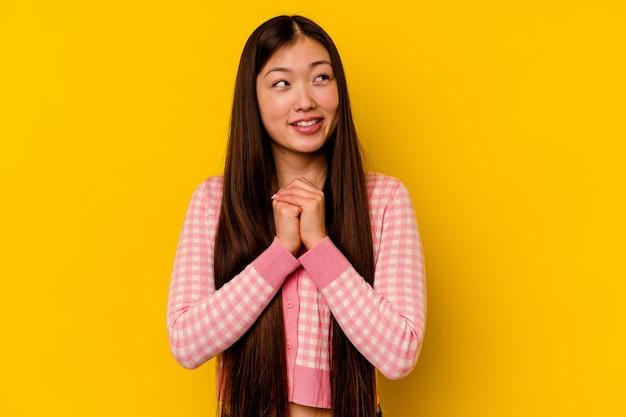 Молодая китаянка, изолированные на желтом фоне, держит руки под подбородком, счастливо смотрит в сторону.