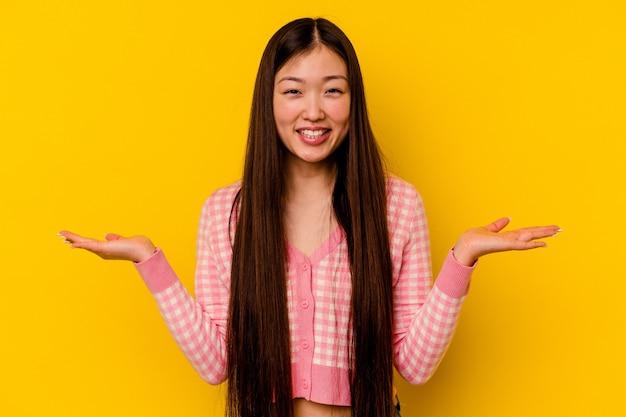 노란색 배경에 고립 된 젊은 중국 여자 팔으로 규모를 만들고 행복 하 고 자신감을 느낀다.