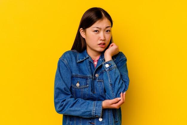 Молодая китаянка изолирована на желтом фоне, массируя локоть, страдая после плохого движения.