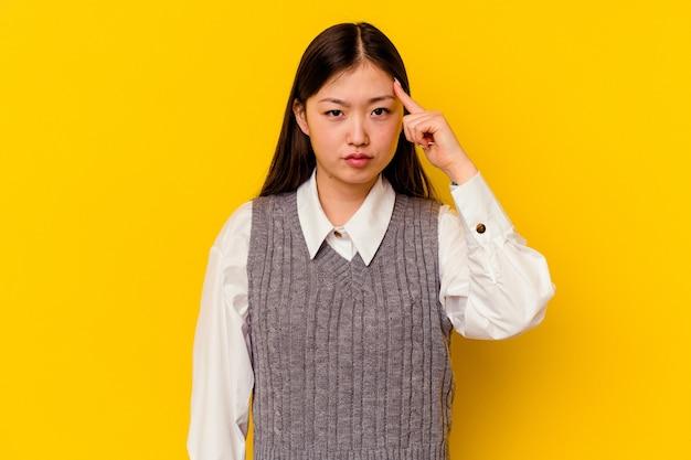 Молодая китаянка изолирована на желтом фоне, указывая висок пальцем, думая, сосредоточилась на задаче.
