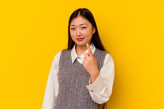 Молодая китаянка изолирована на желтом фоне, указывая пальцем на вас, как будто приглашая подойти ближе.