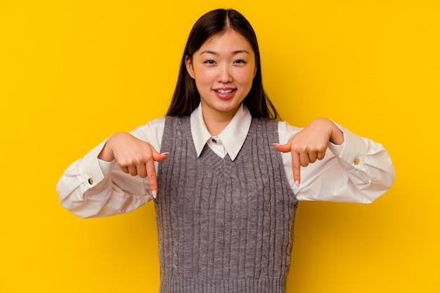 Молодая китаянка, изолированная на желтом фоне, показывает пальцами вниз, позитивное чувство.