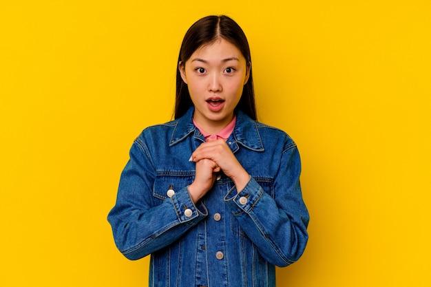 행운을 위해기도하는 노란색 배경에 고립 된 젊은 중국 여자 놀라게 하 고 입을 앞으로 찾고 열기.
