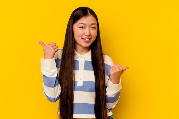 Молодая китаянка изолирована на желтом фоне, поднимая большие пальцы, улыбаясь и уверенно.