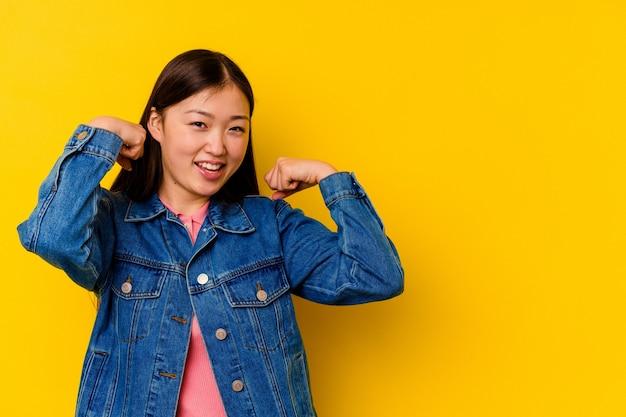 승리, 승자 개념 후 주먹을 올리는 노란색 배경에 고립 된 젊은 중국 여자.
