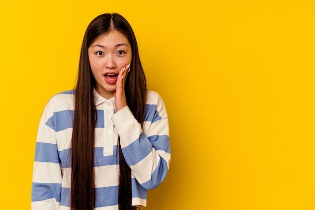 노란색 배경에 고립 된 젊은 중국 여자 큰 소리 질러, 눈을 뜨고 손을 긴장.