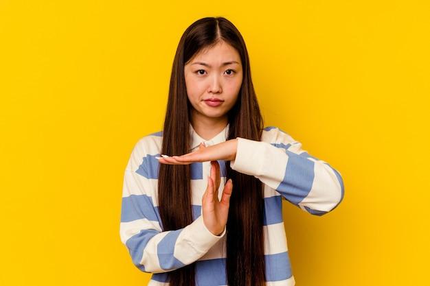 타임 아웃 제스처를 보여주는 노란색 배경에 고립 된 젊은 중국 여자.