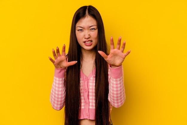 猫を模倣した爪、攻撃的なジェスチャーを示す黄色の背景に分離された若い中国人女性。