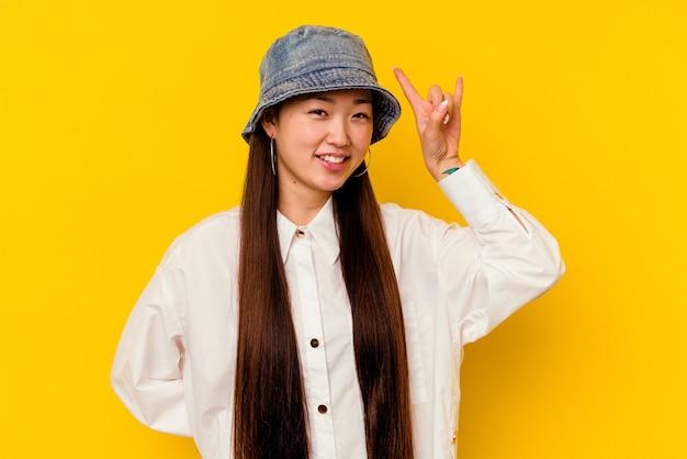 指でロック ジェスチャーを示す黄色の背景に分離された若い中国人女性