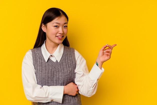 Молодая китаянка, изолированные на желтом фоне, весело улыбаясь, указывая указательным пальцем.