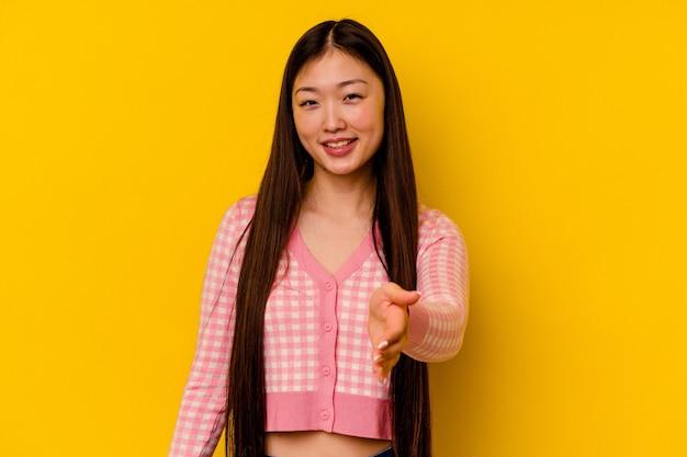 인사말 제스처에 카메라에 손을 스트레칭 노란색 배경에 고립 된 젊은 중국 여자.