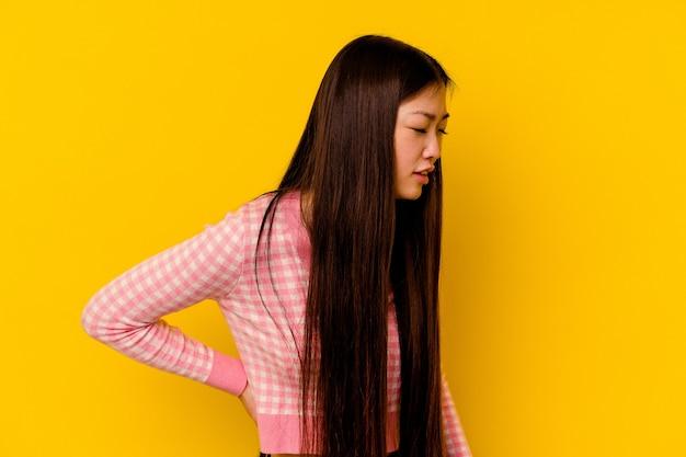 허리 통증을 겪고 노란색 배경에 고립 된 젊은 중국 여자.