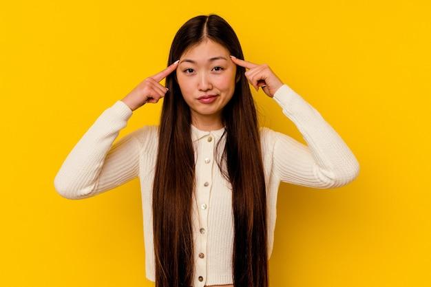 Молодая китаянка, изолированная на желтом, сосредоточилась на задаче, держа указательные пальцы указывая головой.