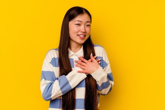 노란색에 고립 된 젊은 중국 여자는 가슴에 손바닥을 눌러 친절식이 있습니다. 사랑 개념.