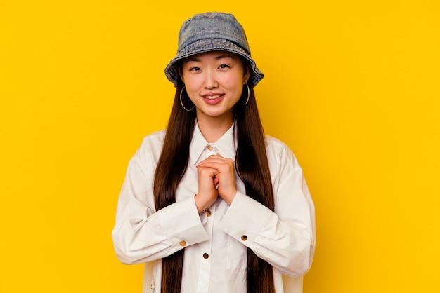 Молодая китаянка, изолированная на желтом, держит руки под подбородком, счастливо смотрит в сторону.